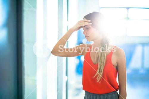 Tired businesswoman leaning on wall