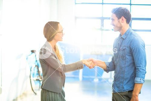 Businesswoman shaking hands with coworker