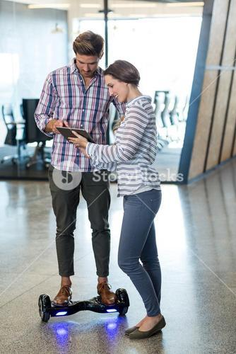 Man on hoverboard using digital tablet with colleagues