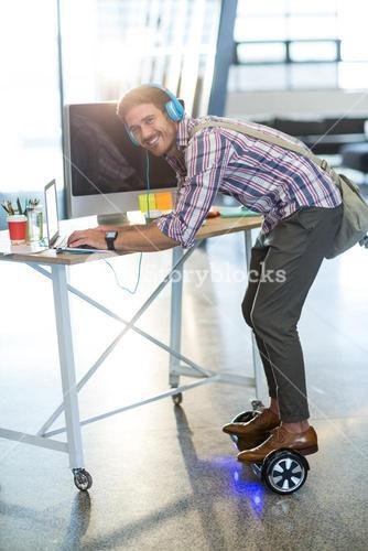 Smiling man standing on hoverboard and using laptop in office