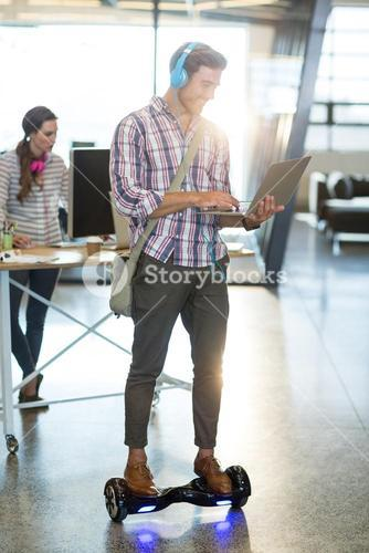 Smiling man standing on hoverboard and using laptop