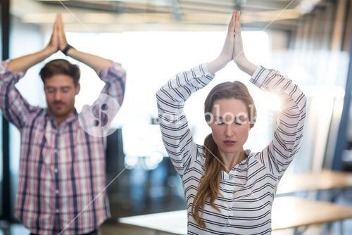 Business people performing yoga