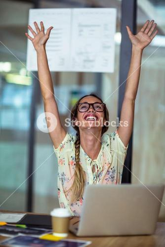 Excited graphic designer sitting with laptop