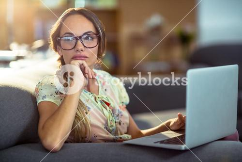Thoughtful woman sitting on sofa and using laptop