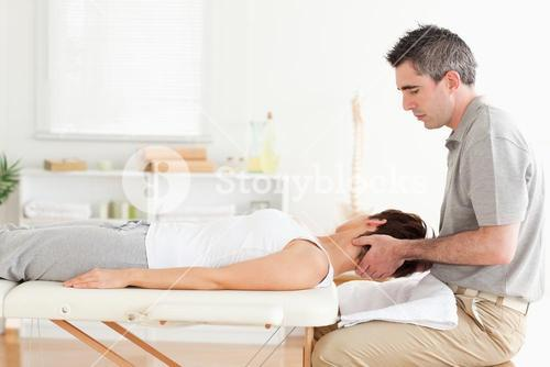 Masseur stretching womans head