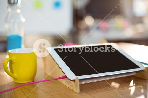 Digital tablet and a cup of coffee on table