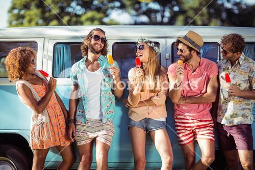 Group of happy friends standing with ice lolly in front of camper van
