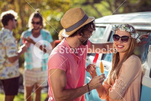 Couple enjoying and eating ice lolly