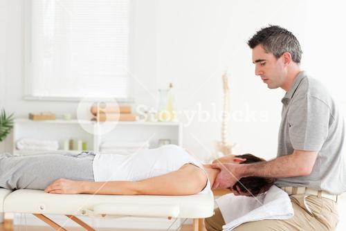 Chiropractor massaging womans neck