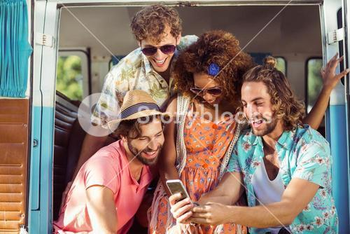 Group of happy friend using mobile phone in campervan