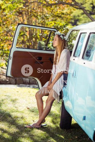Woman with flower wreath sitting in campervan