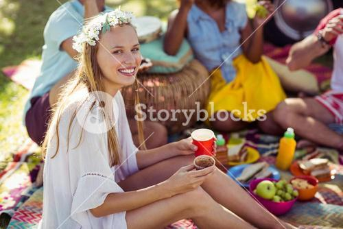 Portrait of woman sitting with coffee cup and cupcake