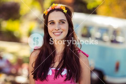 Smiling woman in flower wreath standing in park