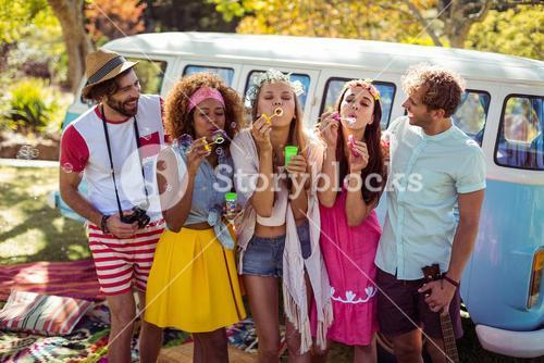 Group of friends blowing bubbles from bubble wand in park