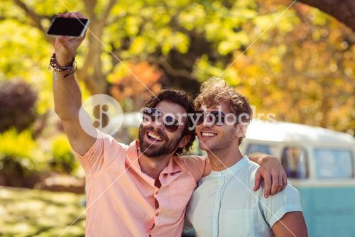 Two male friends taking selfie with mobile phone