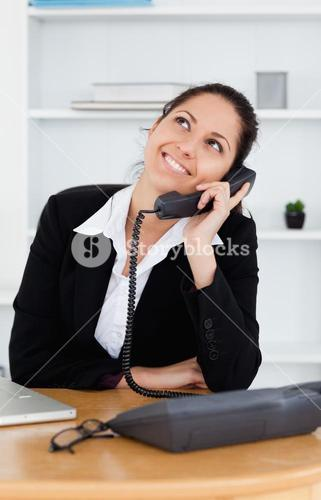 Cheerful cute businesswoman telephoning
