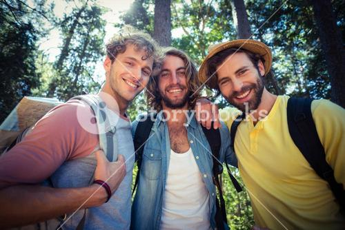 Male friends standing together in forest