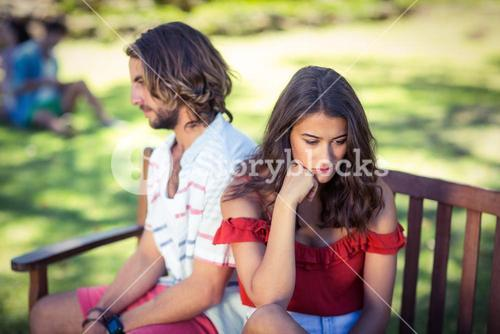 Couple ignoring each other in park
