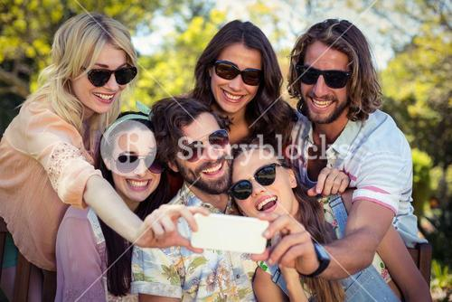 Group of friends taking selfie with mobile phone