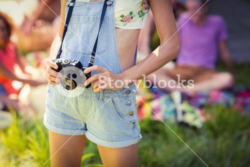 Woman holding camera at campsite