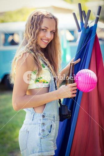 Portrait of woman holding beer bottle at campsite