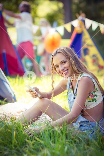 Woman holding mobile phone at campsite