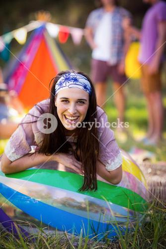 Portrait of woman leaning on beach ball at campsite