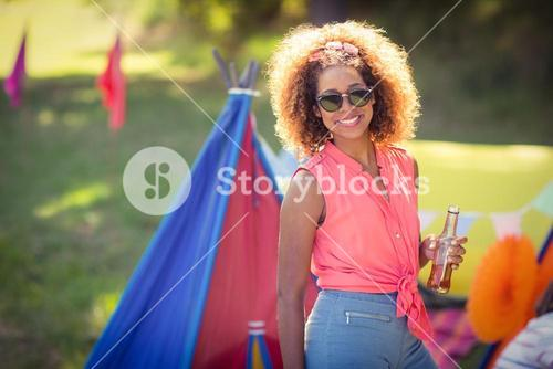Portrait of woman holding beer bottle standing at campsite
