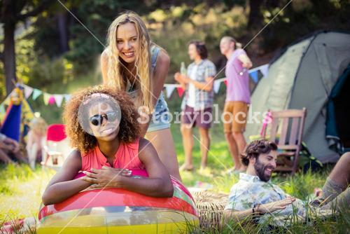 Portrait of friends leaning on beach ball at campsite