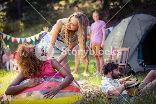 Friends leaning on beach ball at campsite