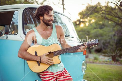 Man playing guitar in front of campervan at campsite