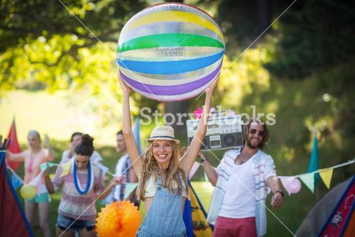 Woman holding beach ball at campsite