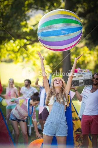 Woman playing with beach ball at campsite