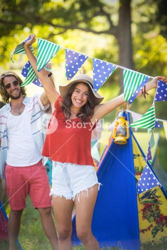 Woman holding bunting at campsite