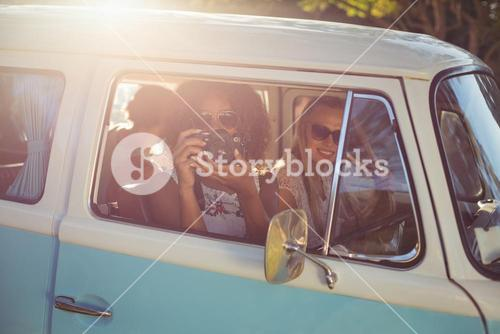 Woman taking photograph while travelling in campervan