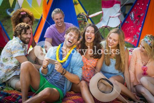 Group of friends using mobile phone at campsite