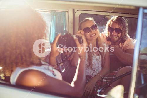 Woman taking photograph of friends in campervan