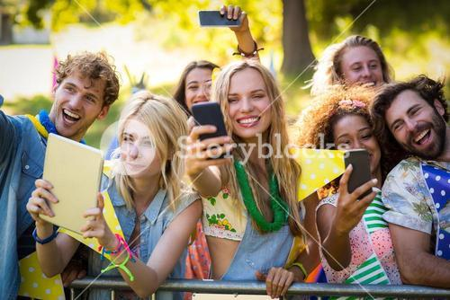 Friends clicking pictures from their mobile phones and digital tablet