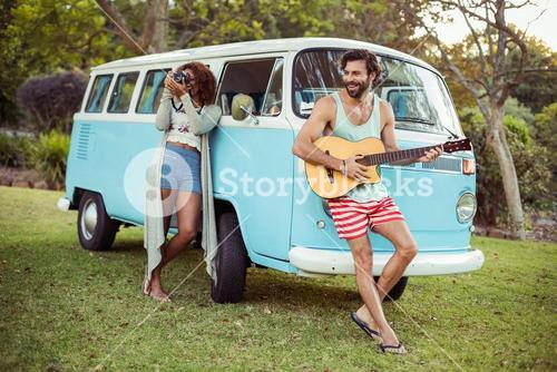 Man playing guitar near campervan and woman photographing beside him