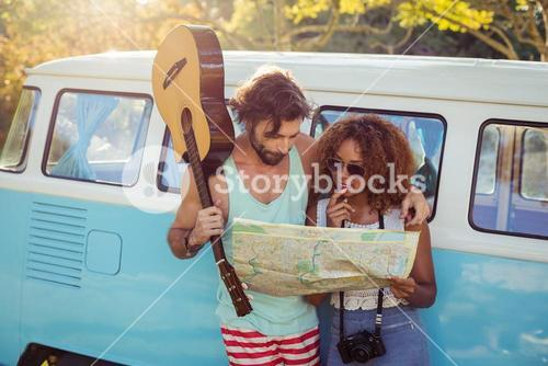 Couple looking at map near campervan