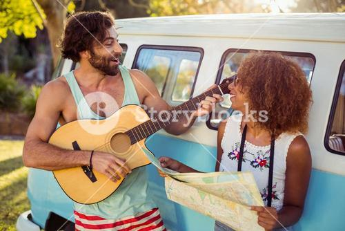Man playing guitar near campervan and woman holding map beside him