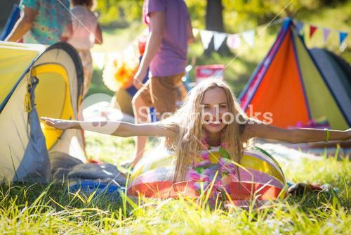 Woman leaning on beach ball at campsite