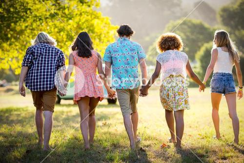 Friends holding hands and walking in park