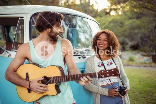 Man playing guitar near campervan while woman standing beside him