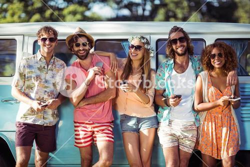 Group of friends holding mobile phone and smiling