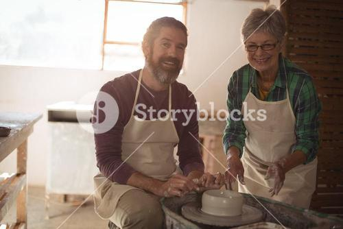 Male and female potter making a pot