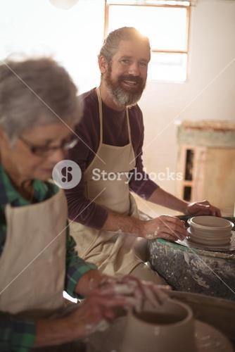 Male potter smiling while making a pot