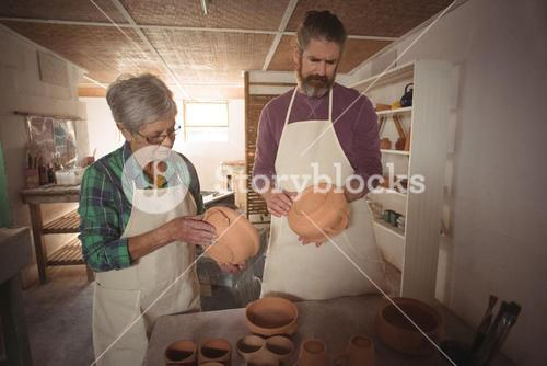 Male and female potter examining a pot