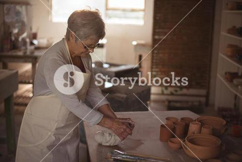 Female potter molding clay