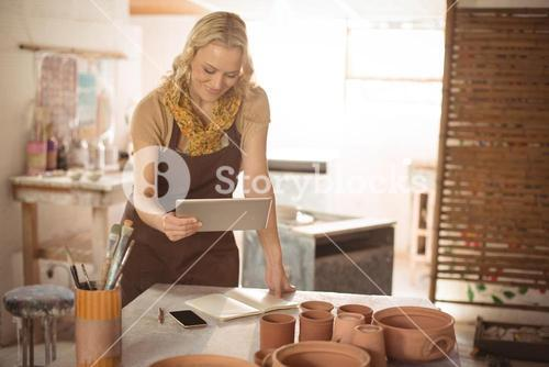 Female potter using digital tablet while working